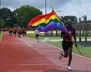 A U.S. Army AIT Soldier carries a rainbow flag during a Pride Observance Month 5K run at Joint Base Langley-Eustis, Virginia, June 20, 2020.