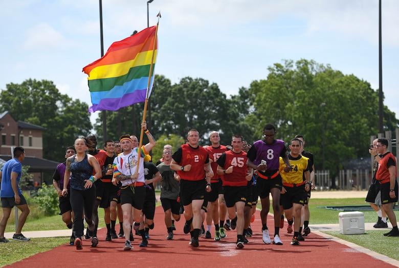 U.S. Army Sgt. Jimmy D. Tingle, Medical Department Activity patient administration specialist, runs with AIT Soldiers while carrying a rainbow flag during a Pride Observance Month 5K run at Joint Base Langley-Eustis, Virginia, June 20, 2020.