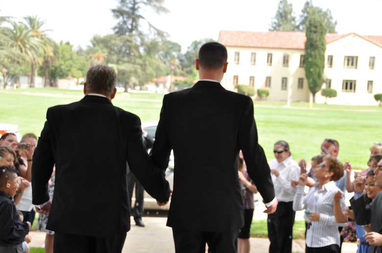 Marvin Tucker, emergency manager, 452nd Air Mobility Wing (left), and his new husband, Joshua Delgado, exit the historic March Air Reserve Base chapel Aug. 3, 2013, to celebrating guests, after the couple became the first same-sex couple to be married on the base