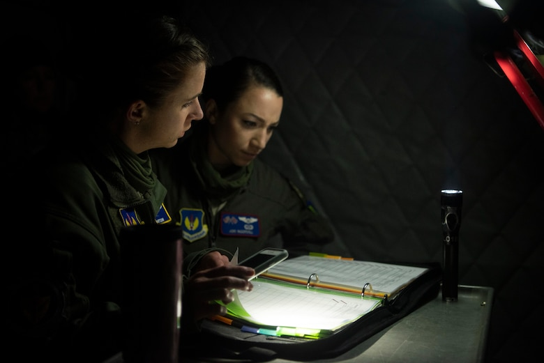 Capt. Marissa Hartoin, 100th Operations Support Squadron chief of wing tactics and instructor pilot, left, and Capt. Jori Ingersoll, 351st Air Refueling Squadron pilot, review KC-135 Stratotanker maintenance records before supporting a strategic bomber mission at RAF Mildenhall, England, June 18, 2020. The 100th Air Refueling Wing provides rapid aerial refueling throughout the U.S. Air Forces in Europe and Air Forces Africa theater. (U.S. Air Force photo by Airman 1st Class Joseph Barron)