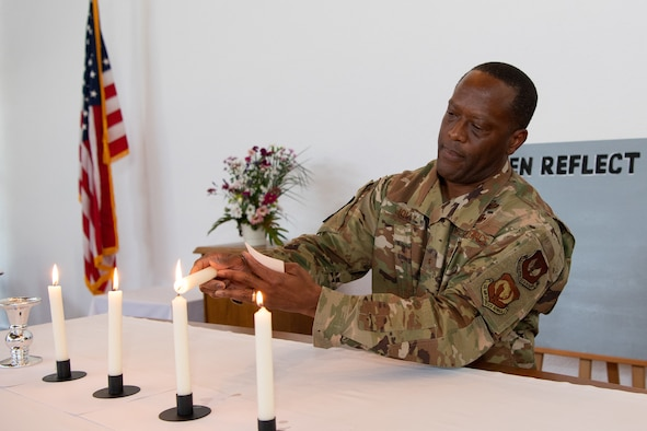 U.S. Air Force Brig. Gen. Ronald E. Jolly Sr., U.S. Air Forces in Europe and Air Forces Africa logistics, engineering and force protection director, lights a candle after giving a speech during the Juneteenth: Vigil for Healing event at Ramstein Air Base, Germany, June 19, 2020.