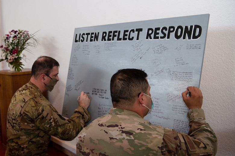 U.S. Air Force Brig. Gen. Mark R. August, 86th Airlift Wing commander, and Chief Master Sgt. Ernesto J. Rendon, 86th AW command chief, sign a message board during the Juneteenth: Vigil for Healing event at Ramstein Air Base, Germany, June 19, 2020.