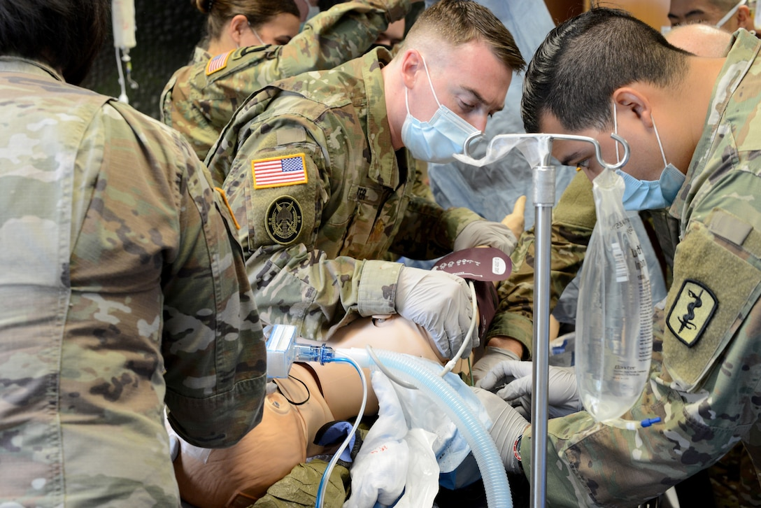 U.S. Army Maj. James Foster, 67th Forward Resuscitative Surgical Team orthopedic surgeon, left, and Spc. Jonathan Lopez, 67th FRST operating room technician, right, place a Hypothermia Prevention and Management Kit under the patient to prepare for transport during a training scenario at the Medical Simulation Training Center, Ramstein Air Base, June 19, 2020.