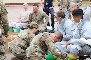 U.S. Air Force Airmen, assigned to the 786th Civil Engineer Squadron Emergency Management flight assist fellow Airmen by taping their Level B suits with protective ChemTape in preparation for entry into a potentially contaminated area at Landstuhl Regional Medical Center, Germany, June 16, 2020.
