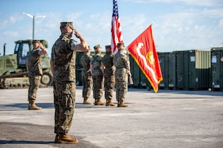 U.S. Marines salute the unit colors during the opening ceremony of SPMAGTF-SC, June 26.