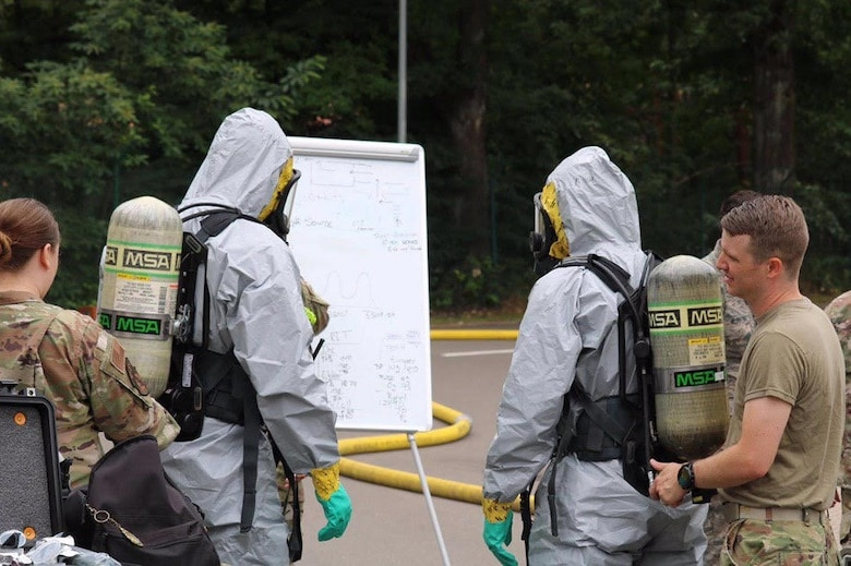 U.S. Air Force Airmen, assigned to the 786th Civil Engineer Squadron Emergency Management Logistics, review the team objectives before entry into a potentially contaminated area at Landstuhl Regional Medical Center, Germany, June 16, 2020.