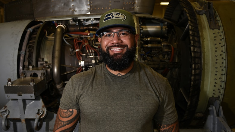 Photo of an engine mechanic in front of an aircraft engine