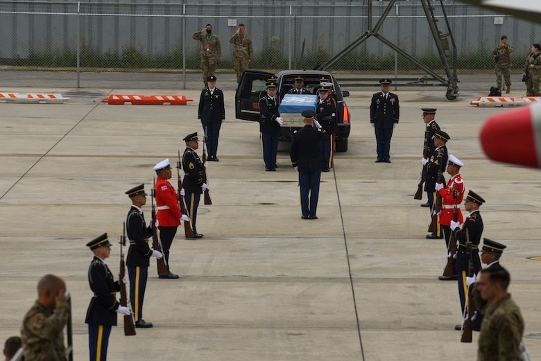 UNC Honor Guard carries a transfer case to an aircraft