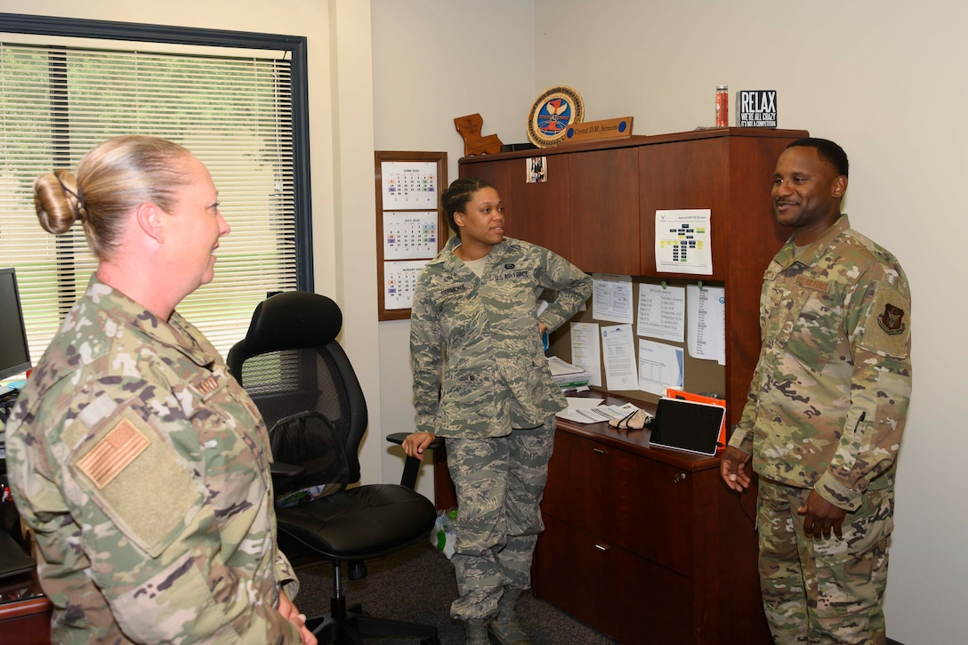 Three Airmen stand in an office, talking.