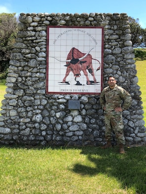 U.S. Air Force Master Sgt. Carlos Torres, 65th Air Base Squadron maintenance superintendent, poses for a photo near his unit's mural. Torres received the Ramstein Air Base Airlifter of the Week award in recognition for his efforts made throughout COVID-19. (Courtesy photo by Master Sgt. Torres)