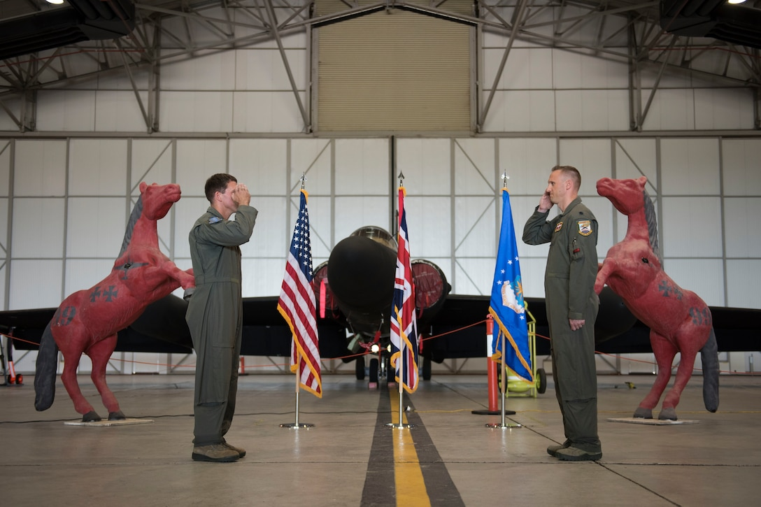 U.S. Air Force Lt. Col. Peter Gryn, right, outgoing 99th Expeditionary Reconnaissance Squadron commander, receives The Meritorious Service Medal from Col. Jason Camilletti, left, 48th Operations Group commander and presiding officer, during a change of command ceremony, at RAF Fairford, England, June 24, 2020. The change of command ceremony is a military tradition that represents a formal transfer of a unit's authority and responsibility from one commander to another. (U.S. Air Force photo by Airman 1st Class Jennifer Zima)