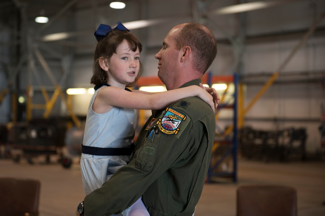 U.S. Air Force Lt. Col. Brian Staniszewski, 99th Expeditionary Reconnaissance Squadron commander, embraces his daughter during a change of command ceremony, at RAF Fairford, England, June 24, 2020. The change of command ceremony is a military tradition that represents a formal transfer of a unit's authority and responsibility from one commander to another. (U.S. Air Force photo by Airman 1st Class Jennifer Zima)