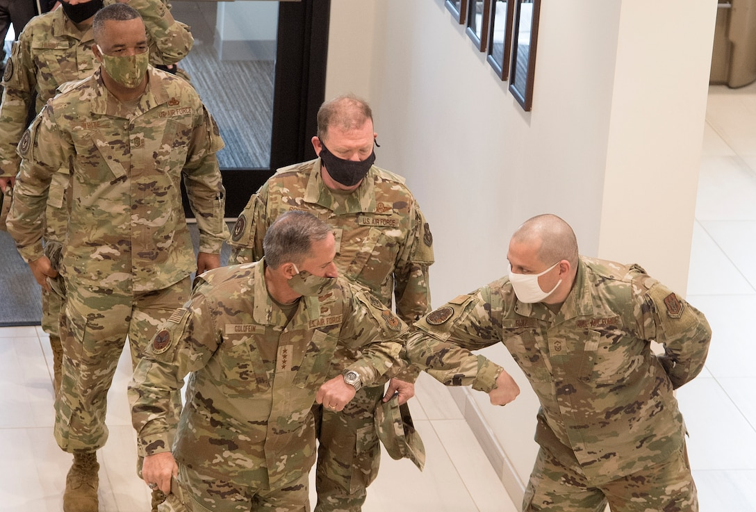 Photo of Air Force Chief of Staff Gen. David L. Goldfein greeting Air Force Reserve Command First Sergeant Senior Master Sgt. Orlando Ruiz, with an elbow bump as a safety measure against COVID-19, while Command Chief Master Sergeant of AFRC Timothy C. White Jr., back left, and Chief of Air Force Reserve Lt. Gen. Richard W. Scobee, looks on, at Robins Air Force Base, Georgia, June 24, 2020.