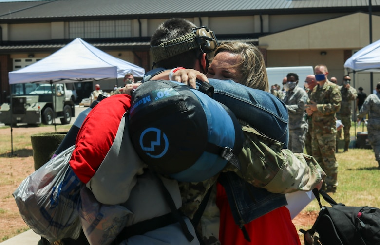 Master Sgt. Jason McGinnis, 317th Aircraft Maintenance Squadron production superintendent, hugs his wife, Lisa McGinnis, after returning from a deployment to Djibouti, Africa, at Dyess Air Force Base, Texas, May 18, 2020. Family members have access to a multitude of resources across the base to help them while their military spouses are deployed. (U.S. Air Force photo by Staff Sgt. David Owsianka)
