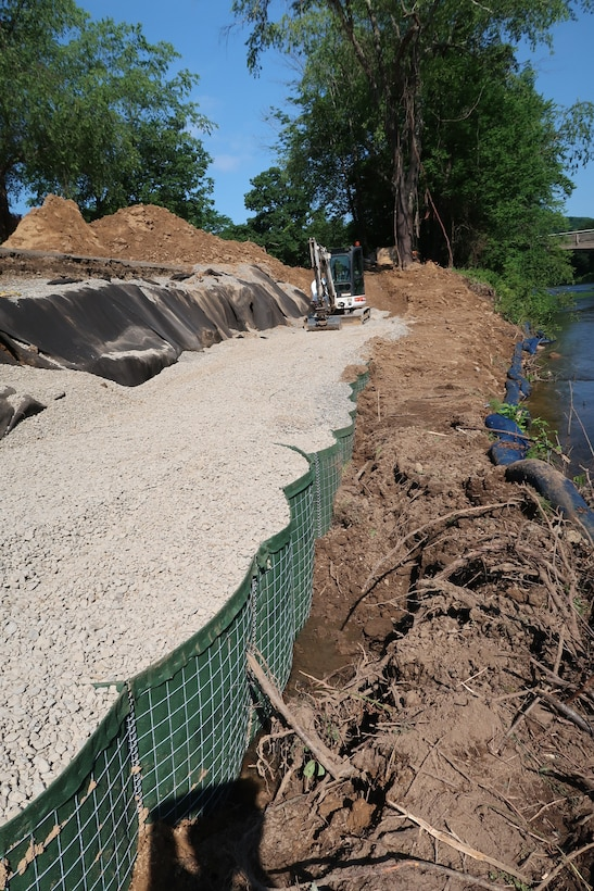 Heavy construction machinery fills temporary barriers with stone along the access road to a dam in Tionesta, Pennsylvania June 25, 2020.