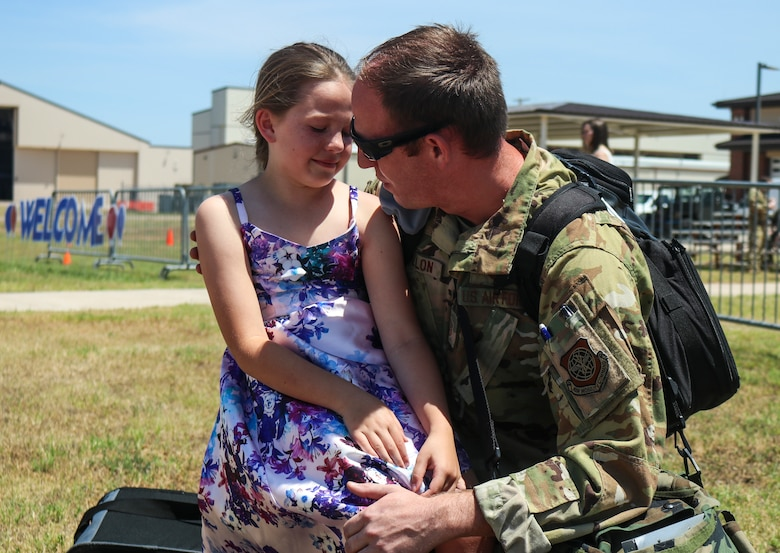 Master Sgt. Ryan Fallon, 40th Airlift Squadron operations superintendent, holds his daughter Mikaela Fallon, 8-years-old, after returning from a deployment to Djibouti, Africa, at Dyess Air Force Base, Texas, May 18, 2020. The new deployment schedule provides Airmen with the opportunity to seek personal growth and professional development while having a better family balance. (U.S. Air Force photo by Staff Sgt. David Owsianka)