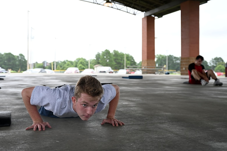 Airman 1st Class Isaiah Miller, 19th Airlift Wing Public Affairs mass communications apprentice, does a push-up during a Vital 90 course as part of Wingman Day at Little Rock Air Force Base.