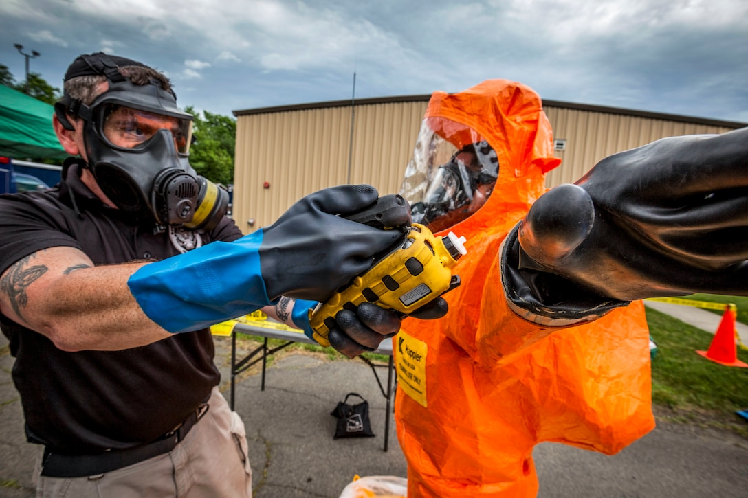 One soldier holds an instrument up to another soldier, who is wearing an orange protective suit.