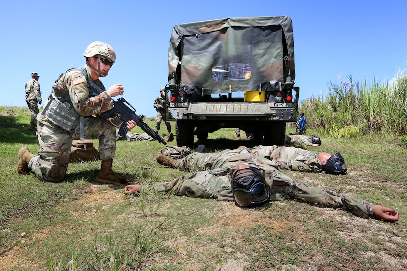 Two officer candidates lie on their backs behind a truck in a field, while one, holding a rifle, kneels beside them.