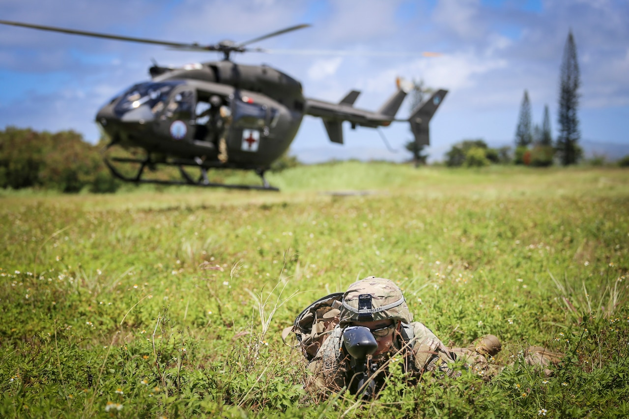 An officer candidate dressed for combat lies face-down in a grassy field as a helicopter marked with a red cross lands in the background.