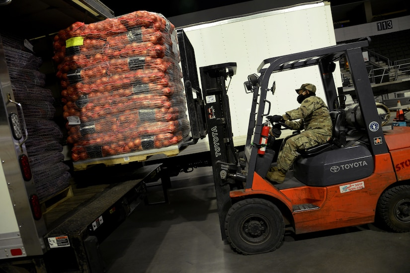A soldier uses a forklift to lift a pallet of food.