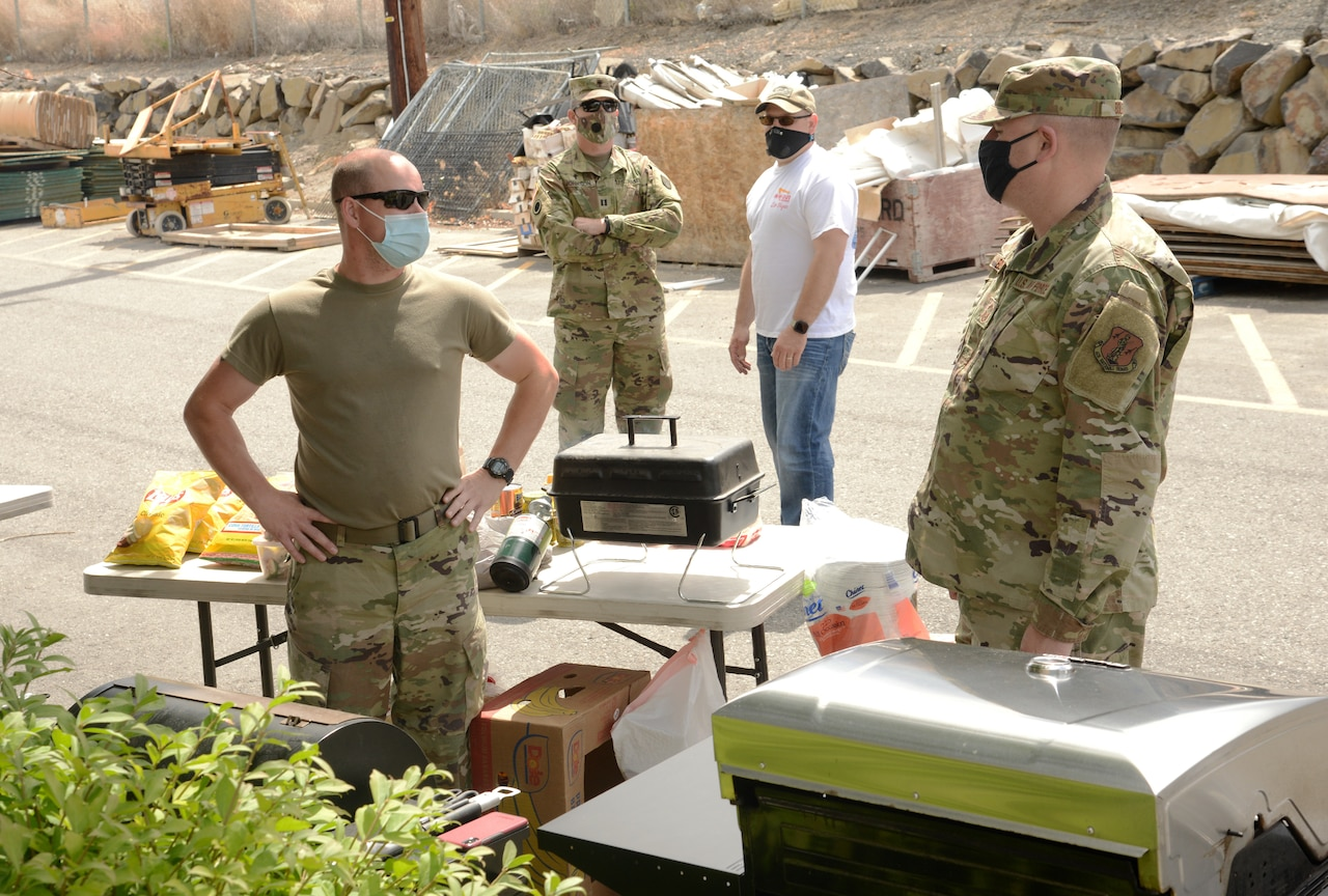 Guardsmen wearing face masks stand next to a table with food on it.