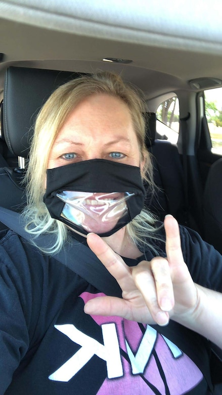"""A woman wearing a face mask gives the sign for """"I love you."""""""