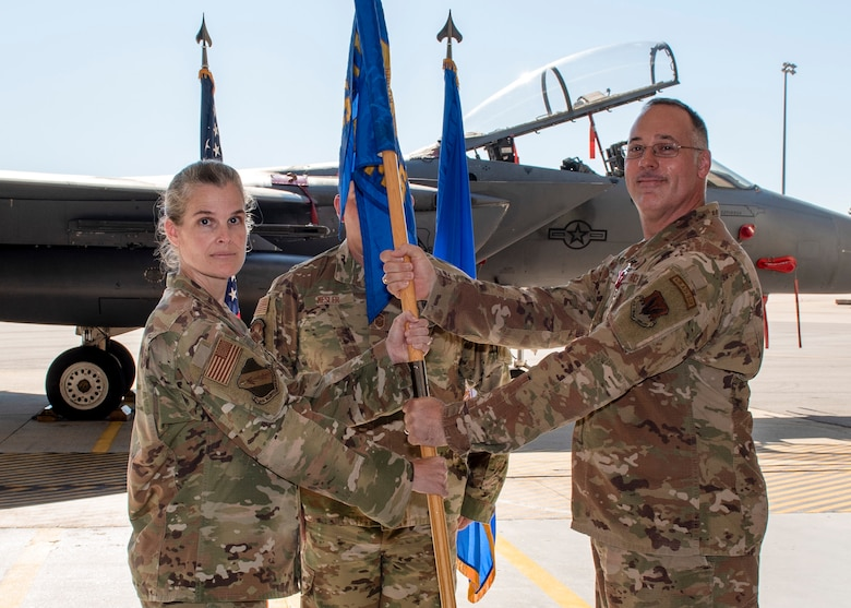 Maj. John R. Ware, 4th Equipment Maintenance Squadron commander (right), passes the guidon flag to Col. Leah R. Fry, 4th Maintenance Group commander (left),during a change of command ceremony at Seymour Johnson Air Force Base, North Carolina, June 26, 2020.