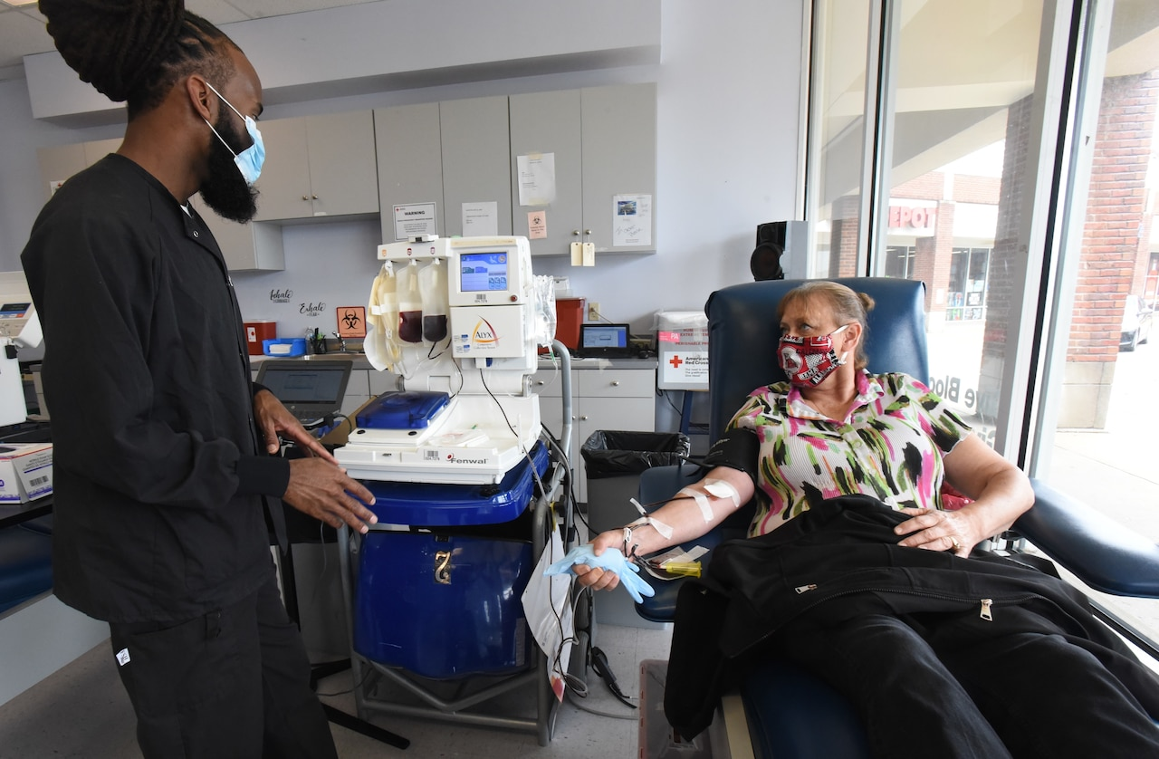 A technician speaks with a woman lying on a blood-donation table with a catheter in her arm.