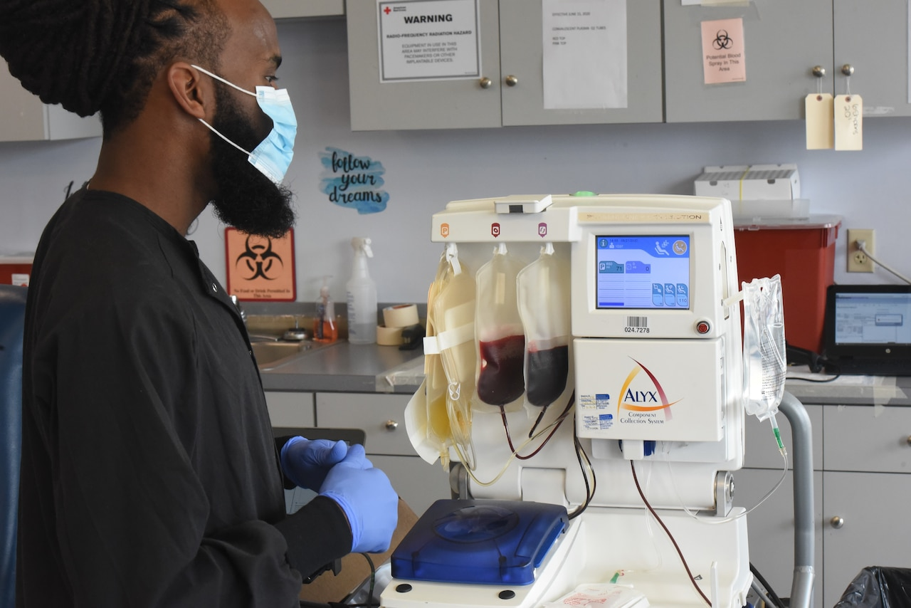 A technician watches as a machine separates whole blood into three components.