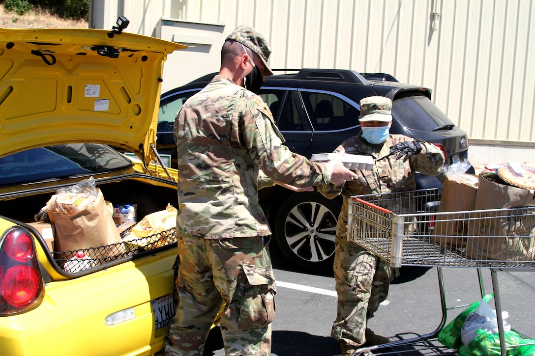 Two soldiers place packages of food into the trunk of a car.