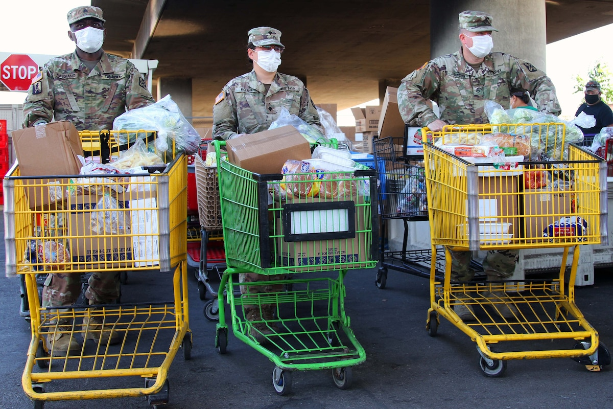 Three service members wearing face masks and gloves prepare to deliver grocery carts filled with food to waiting vehicles.