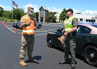 Spc. Ryan Stone, 197th Field Artillery Brigade, New Hampshire Army National Guard, and Trooper Doug Bailey of Troop B, New Hampshire State Police, work a traffic post at a mobile food pantry conducted on June 26 in Manchester.