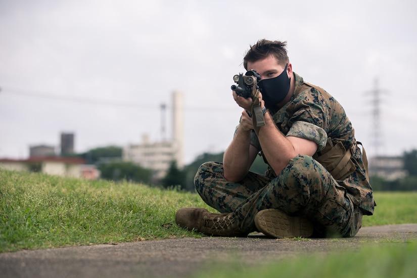 A seated Marine practices marksmanship fundamentals.