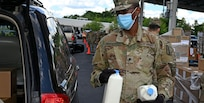 Spc. Nelson Marwanga, a nodal network systems operator -maintainer with the 372nd Signal Company, New Hampshire Army National Guard, distributes fresh milk at a mobile food pantry held on June 26 in Manchester.