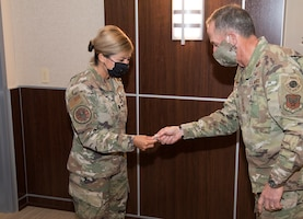 Photo of Air Force Chief of Staff Gen. David L. Goldfein, giving a coin to Air Force Reserve Command Public Health Officer Lt. Col. Jessica Dees for her contributions in the battle against COVID-19, at Robins Air Force Base, Georgia, June 24, 2020.