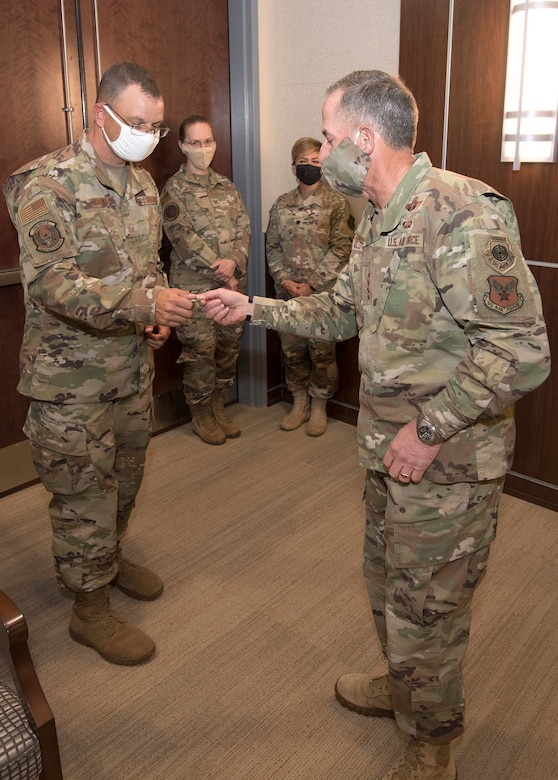 Photo of Air Force Chief of Staff Gen. David L. Goldfein, giving a coin to Master Sgt. Robert Crowe, a Branch Superintendent for A6 in Air Force Reserve Command, for his contributions in boosting teleworking capabilities during the COVID-19 pandemic at Robins Air Force Base, Georgia, June 24, 2020.