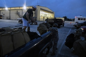 33rd Civil Engineer Squadron Reserve Citizen Airmen, Senior Master Sgt. Stephen Johnson, fire chief (left), Senior Airman Rene Ruiz, firefighter, and Master Sgt. Jane Cummings, unit deployment manager, load bags into a pickup as squadron members prepare to deploy to Southwest Asia June 28, 2020, at Joint Base San Antonio-Lackland, Texas.