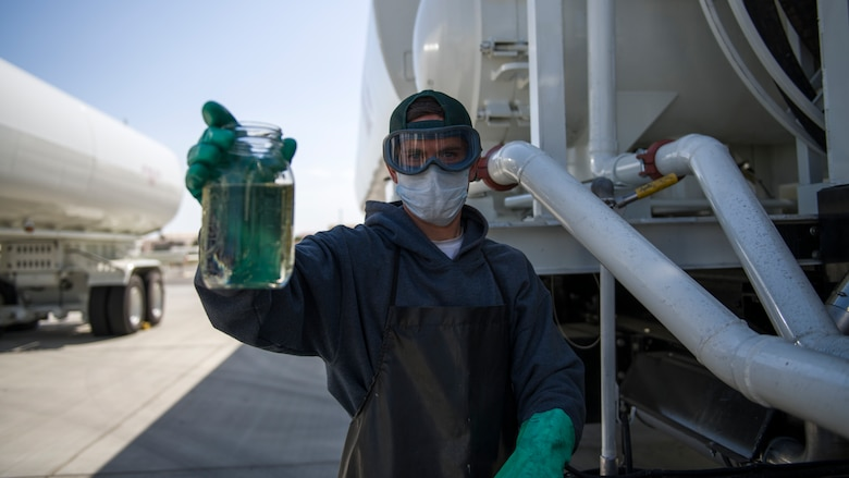 Daniel Beasley, a Fuels Distribution Service Operator, 412th Logistics Readiness Squadron, holds up a jar of jet fuel during a filter system check of the Large Capacity Refuel Vehicle at Edwards Air Force Base, June 26. (Air Force photo by Giancarlo Casem)