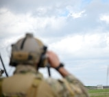 A U.S. Air Force joint terminal attack controller assigned to the 320th Special Tactics Squadron watches  an F-16 Fighting Falcon assigned to the 13th Fighter Squadron fly over a target at Draughon Range, near Misawa Air Base, Japan, June 15, 2020. The JTACs and the F-16 pilots teamed up to conduct close air support training to maintain their proficiency. Due to safety precautions taken in response to the coronavirus, many training opportunities have been postponed or cancelled. Fortunately, Misawa Air Base has Draughon Range to conduct some of the missed training and allowed the JTACs to come from Kadena Air Base to maintain their currency on fixed-wing CAS. (U.S. Air Force photo by Tech. Sgt. Timothy Moore)