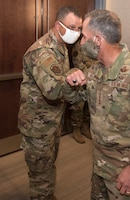 Photo of Air Force Chief of Staff Gen. David L. Goldfein, elbow bumping Master Sgt. Robert Crowe, a branch superintendent for A6 in Air Force Reserve Command, after giving him a coin for his contributions in boosting teleworking capabilities during the COVID-19 pandemic at Robins Air Force Base, Georgia, June 24, 2020.