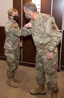 Photo of Air Force Chief of Staff Gen. David L. Goldfein, elbow bumping Air Force Reserve Command Public Health Officer Lt. Col. Jessica Dees after giving her a coin for her contributions in the battle against COVID-19 at Robins Air Force Base, Georgia, June 24, 2020.
