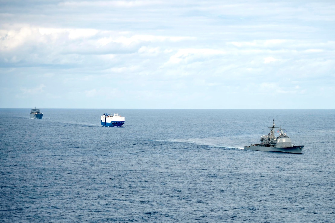 USS Vella Gulf (CG 72), right, the vehicle carrier MV Resolve, center, and the Military Sea Lift Command (MSC) roll-on roll-off cargo ship USNS Benavidez (T-AKR 306) steam in formation