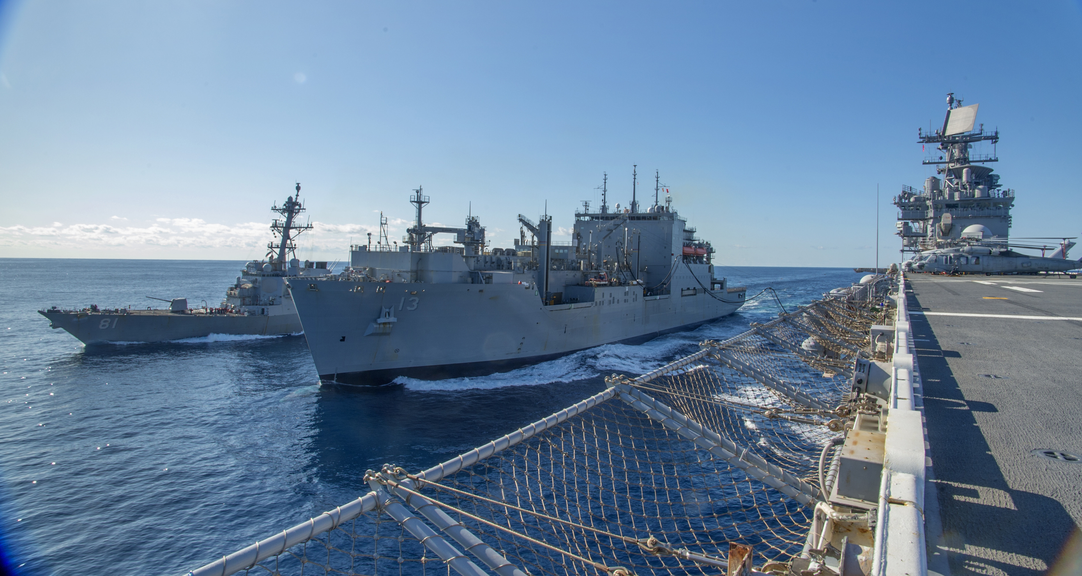 USNS Medgar Evers (T-AKE-13) refuels the Wasp-class amphibious assault ship USS Iwo Jima (LHD 7) to her port side and USS Winston S. Churchill (DDG 81) to her starboard side during a replenishment-at-sea, February 23, 2020