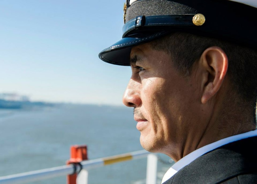 A man wearing a cap looks into the distance.
