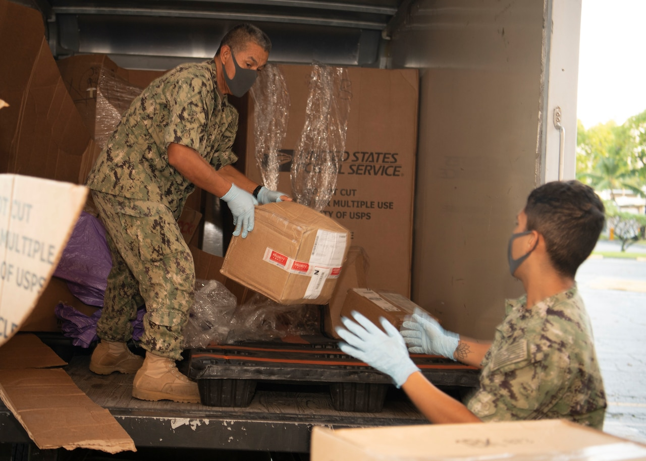 A sailor wearing a face mask unloads a box from a truck and gives it to another sailor, who is also wearing a face mask.