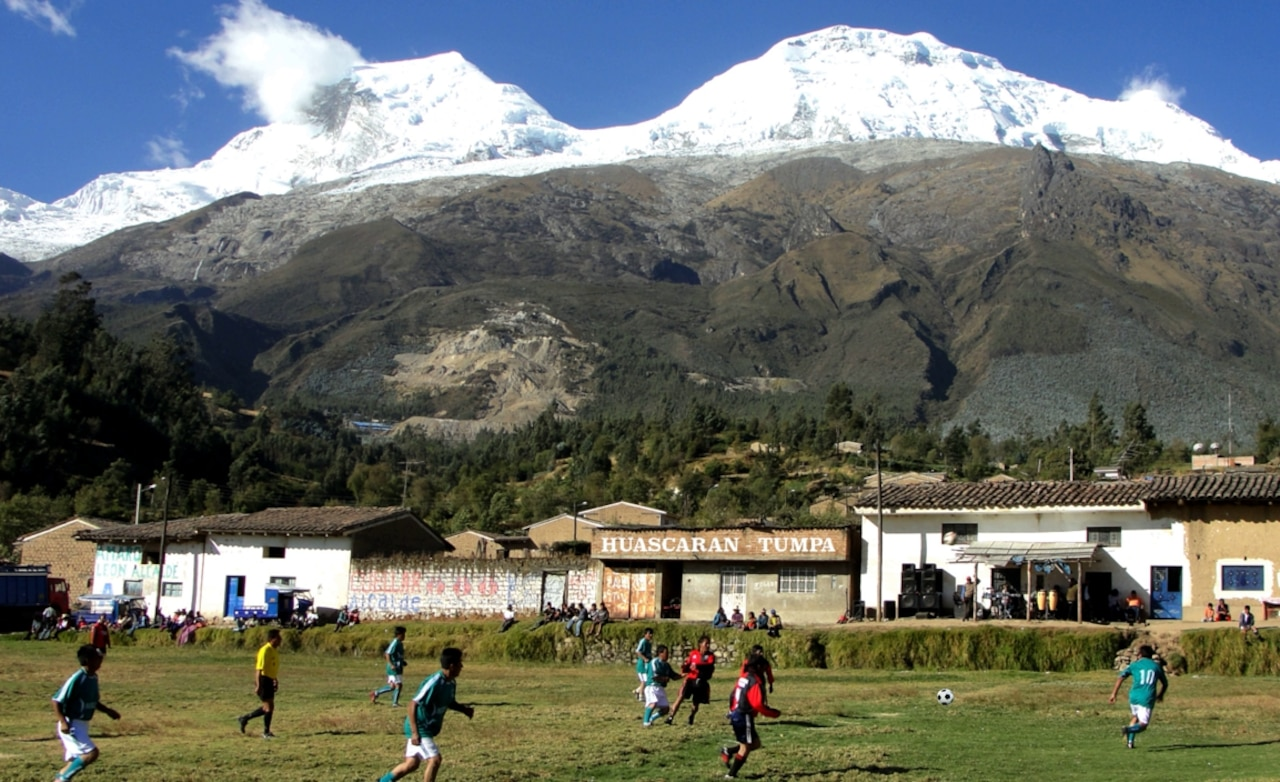 Soccer players run on a field with small buildings along the edge. Snow-capped mountains loom in the background.