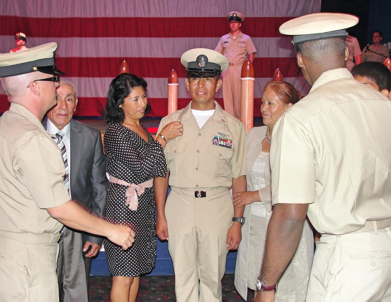 People surround a sailor in his dress uniform.