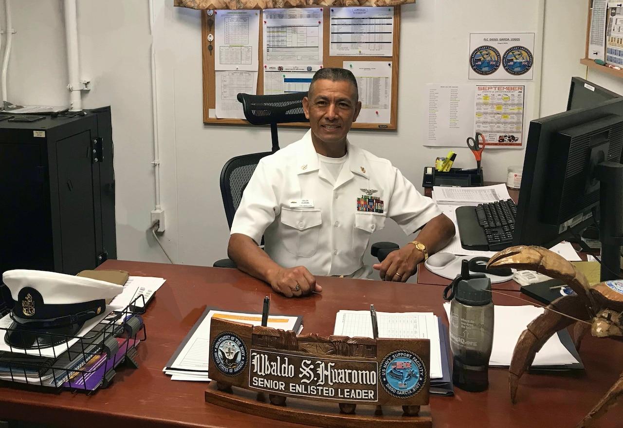 A sailor sits behind a desk.