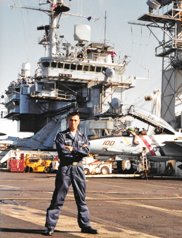 A sailor stands with arms crossed on the deck of an aircraft carrier.